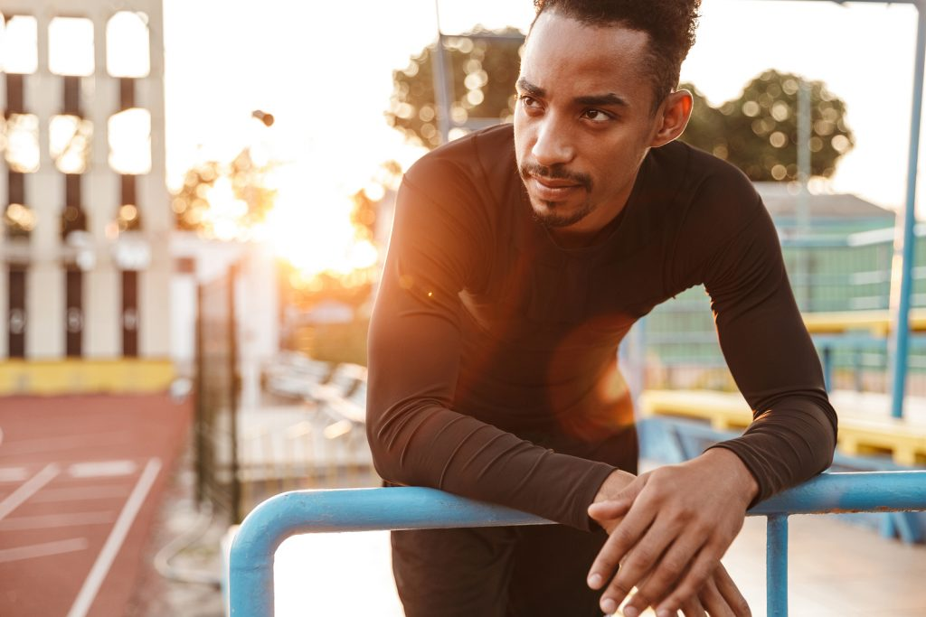 Image of concentrated african american man standing by railing at sports stadium outdoors after stepping away due to social anxiety. Willow Counseling therapists help treat anxiety disorders of all kinds in Nashville, TN.