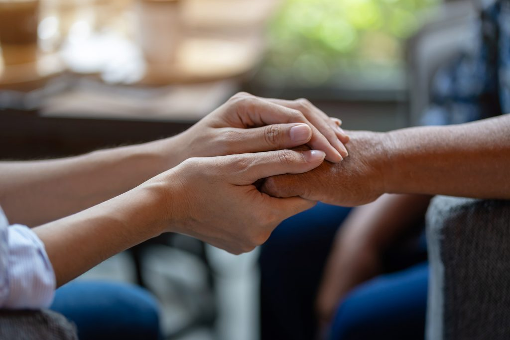 Hand of younger hands holding older hands. Represents holding space for Sexual assault victim counseling, therapy for sexual assault in Nashville, TN.