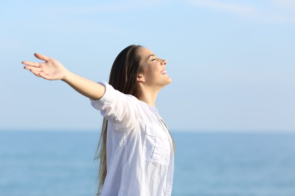 Woman in white shirt stretching her arms out and looking up to the sky in front of ocean