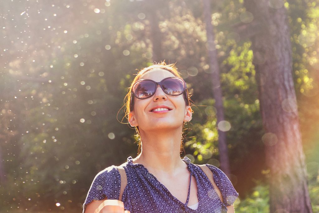 Young woman with sunglasses looking up and smiling. She received anxiety treatment using Cognitive Behavioral Therapy (CBT) and learned to cope with anxious thoughts at Willow Counseling in Nashville, TN.