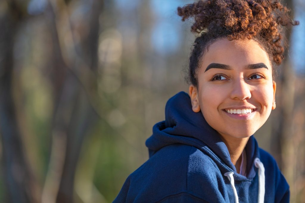 Photo of woman wearing a blue hooded sweat shirt smiling at the camera in nature | Relaxation strategies to cope with secondary traumatic stress | Anxiety treatment & trauma therapy with an EMDR trained counselor in Nashville, TN