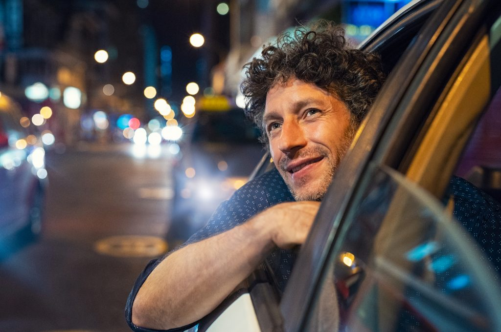 Man smiling looking out of a car window in the city after going to therapy or counseling