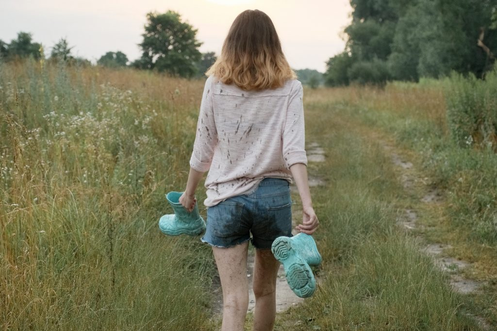 Photo of woman walking on rural road holding teal rain boots after going to counseling   Willow Counseling   Nashville, TN