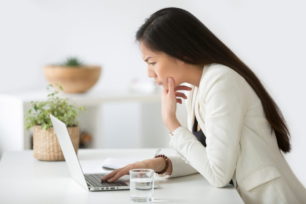 Serious asian woman workin on a laptop | Symptoms of burnout | Willow Counseling | 37212